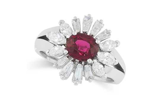 A RUBY AND DIAMOND CLUSTER RING set with an oval cut ruby of 1.46 carats in a border of tapered