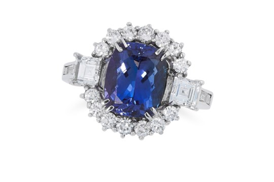 A TANZANITE AND DIAMOND DRESS RING set with an oval cushion cut tanzanite, in a cluster of round