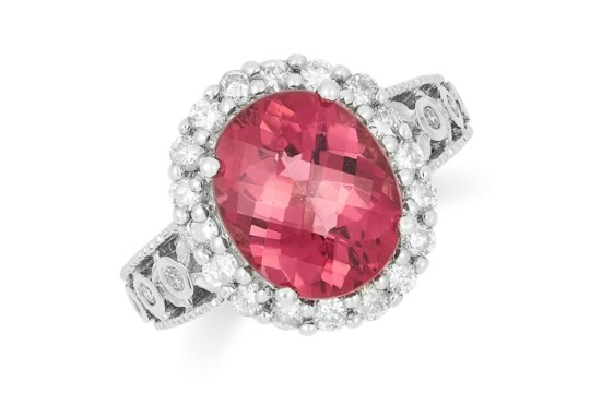 A PINK TOURMALINE AND DIAMOND DRESS RING, set with a faceted oval cut tourmaline and round cut