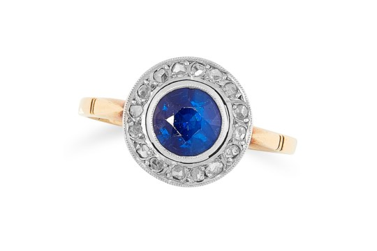 A SAPPHIRE AND DIAMOND CLUSTER RING set with a round cut sapphire in a border of rose cut