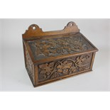 Lot 391 - A carved oak candle box, decorated with vine leaves and grapes 31.5cm wide