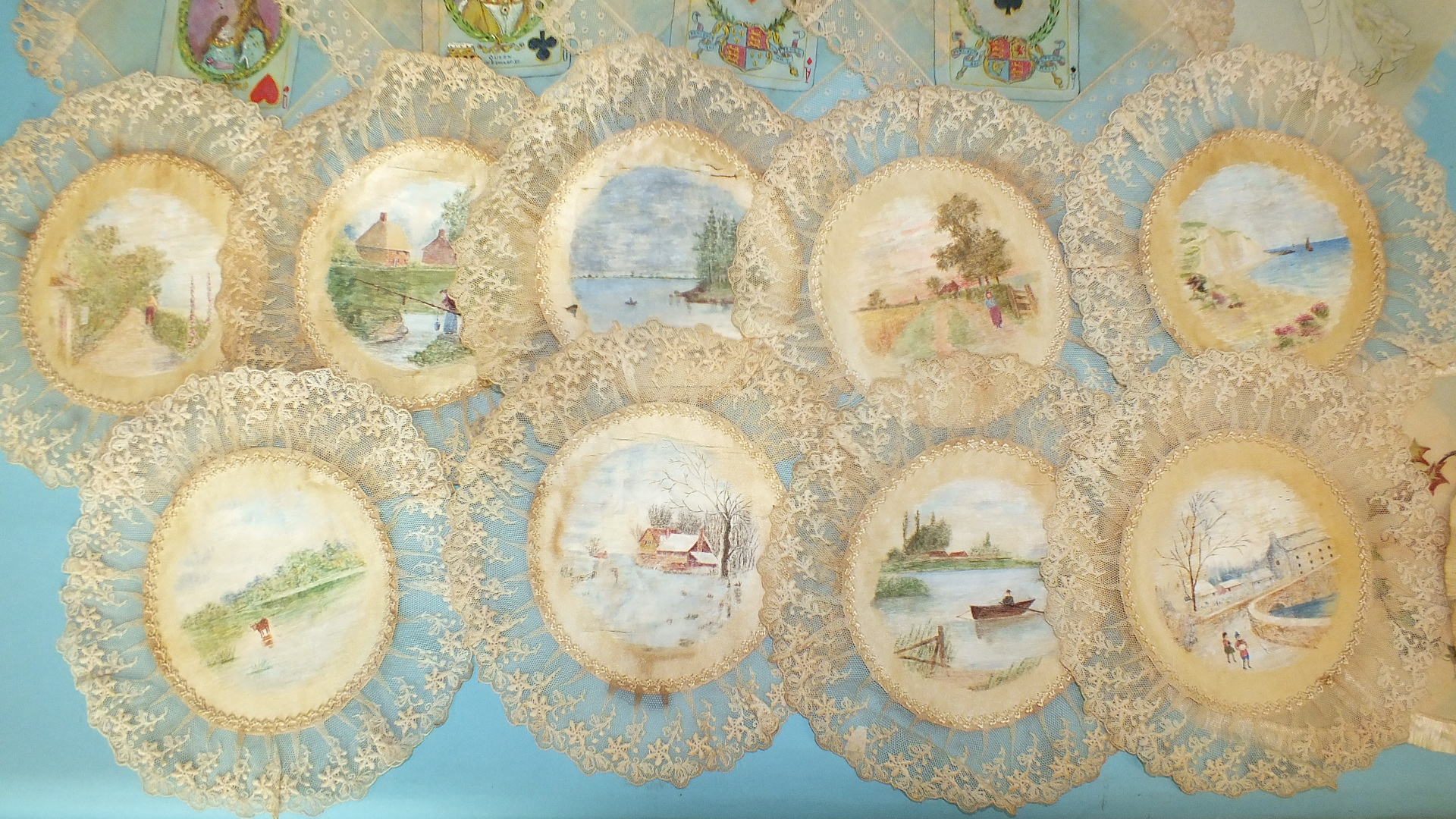 Lot 494 - A collection of silk and lawn mats, mostly trimmed with lace, the centres painted with romantic