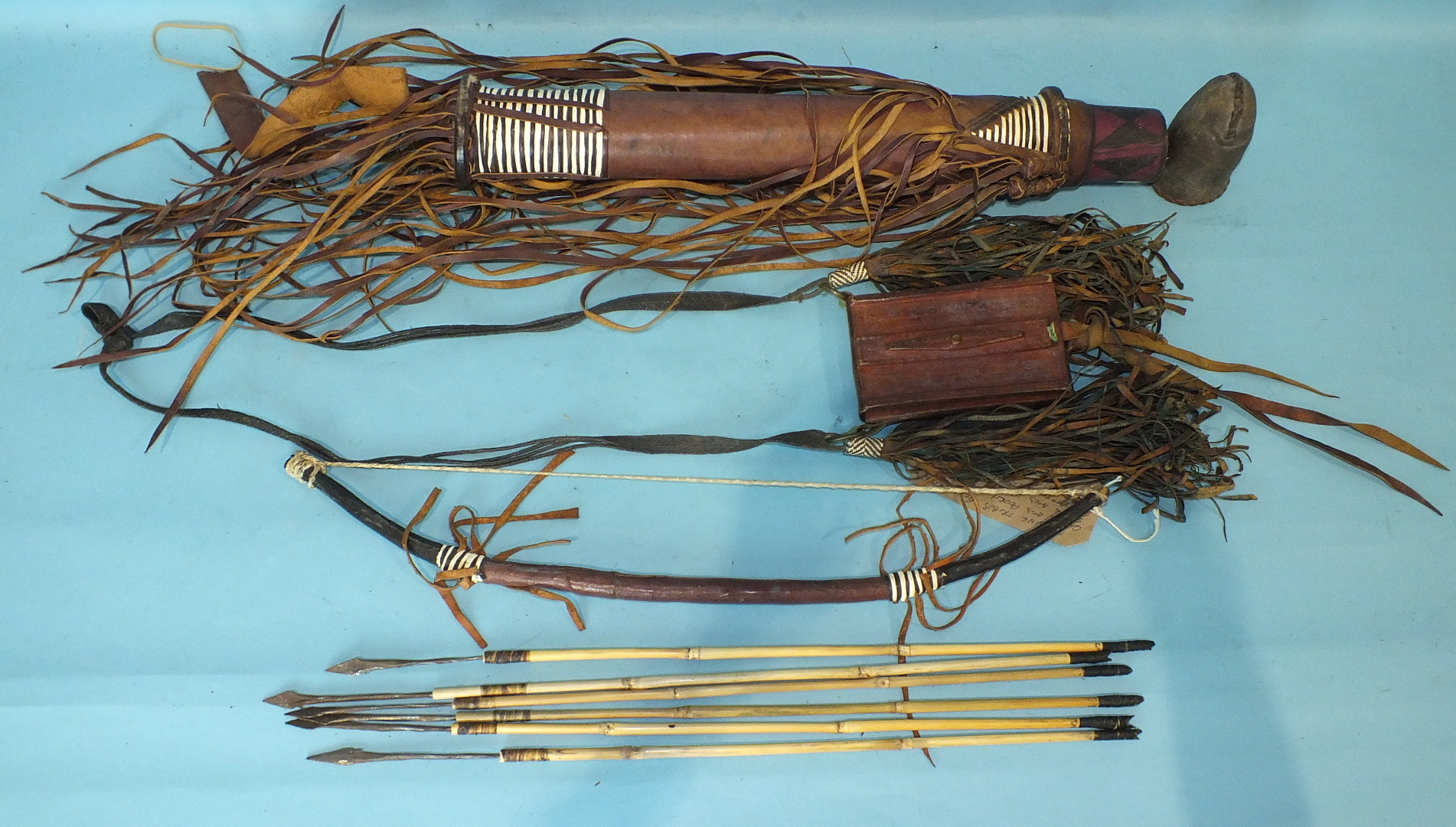Lot 543 - A 20th century African tribal bow, arrows and pouch constructed of leather.