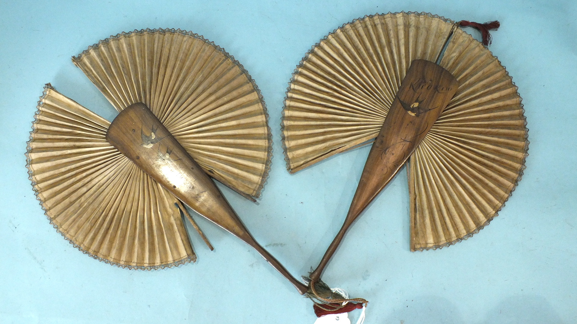 Lot 490 - An early-20th century olive-wood-handle cockade fan, inscribed 'Ricordo', above an inlaid swallow on