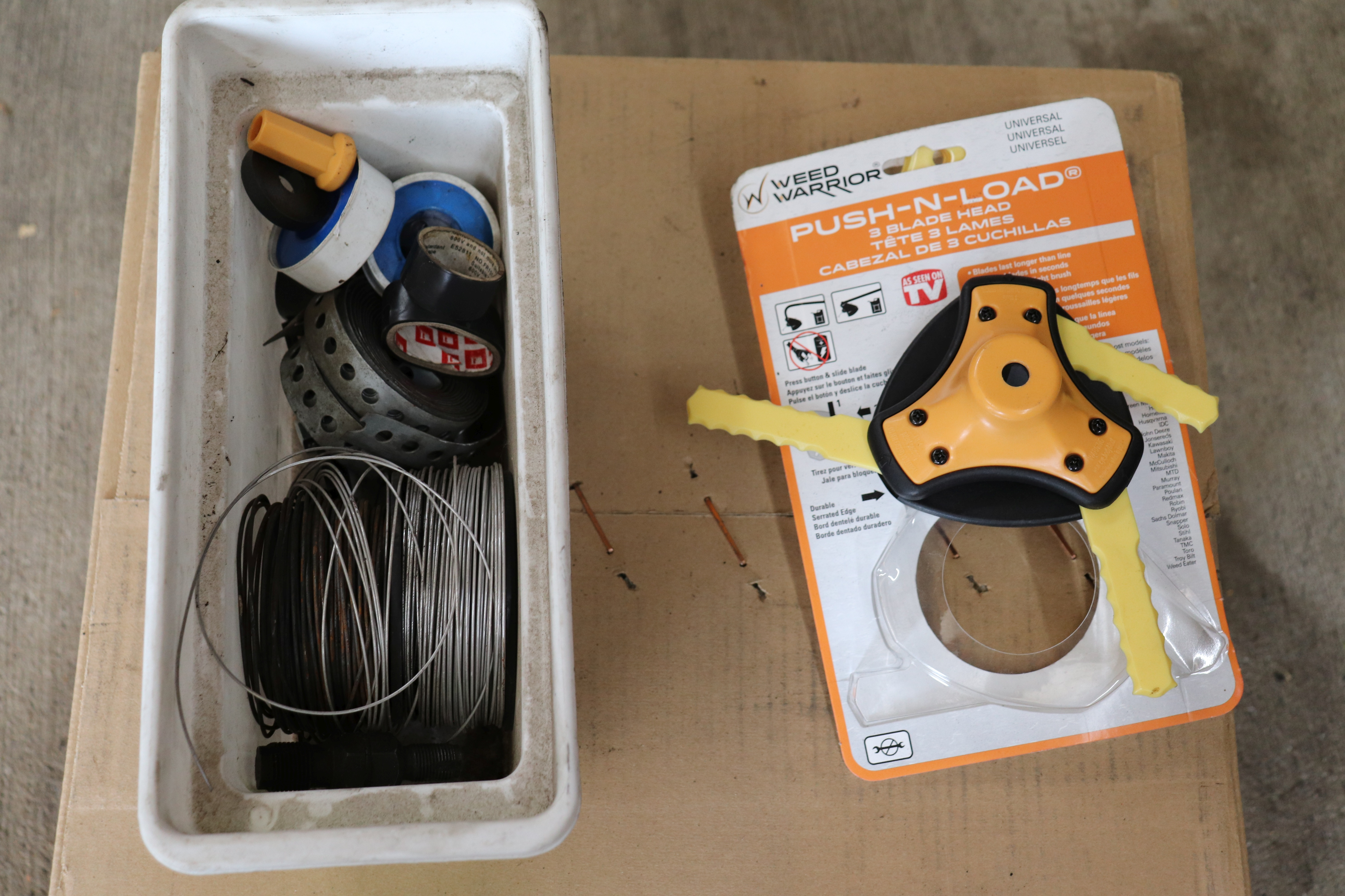 Box of wire and electrical tape and a push and load three-headed weed wacker head