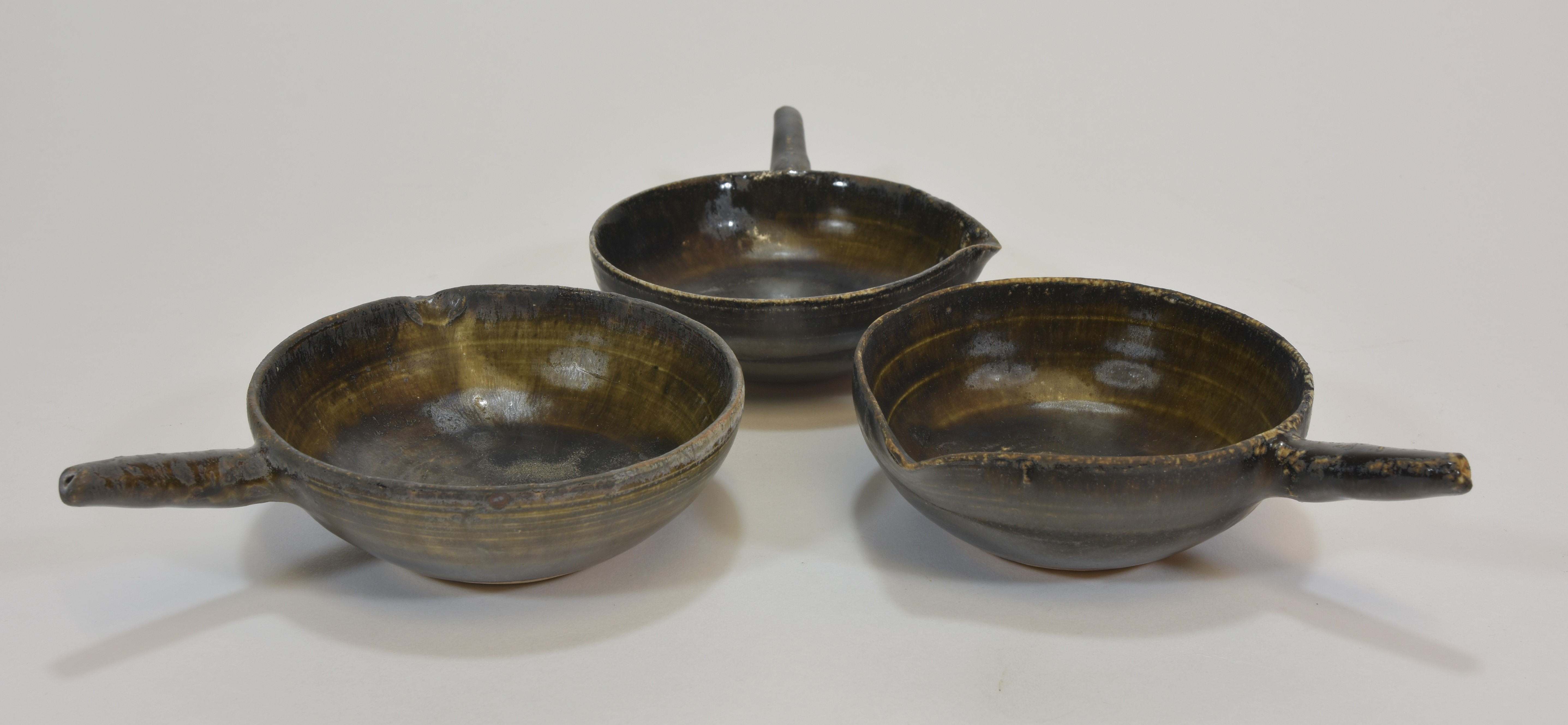 Lot 21 - Three 12th century Southern Song dynasty brown glazed bowls with handles 10cm diameter (3)宋朝時期 灰釉小碗