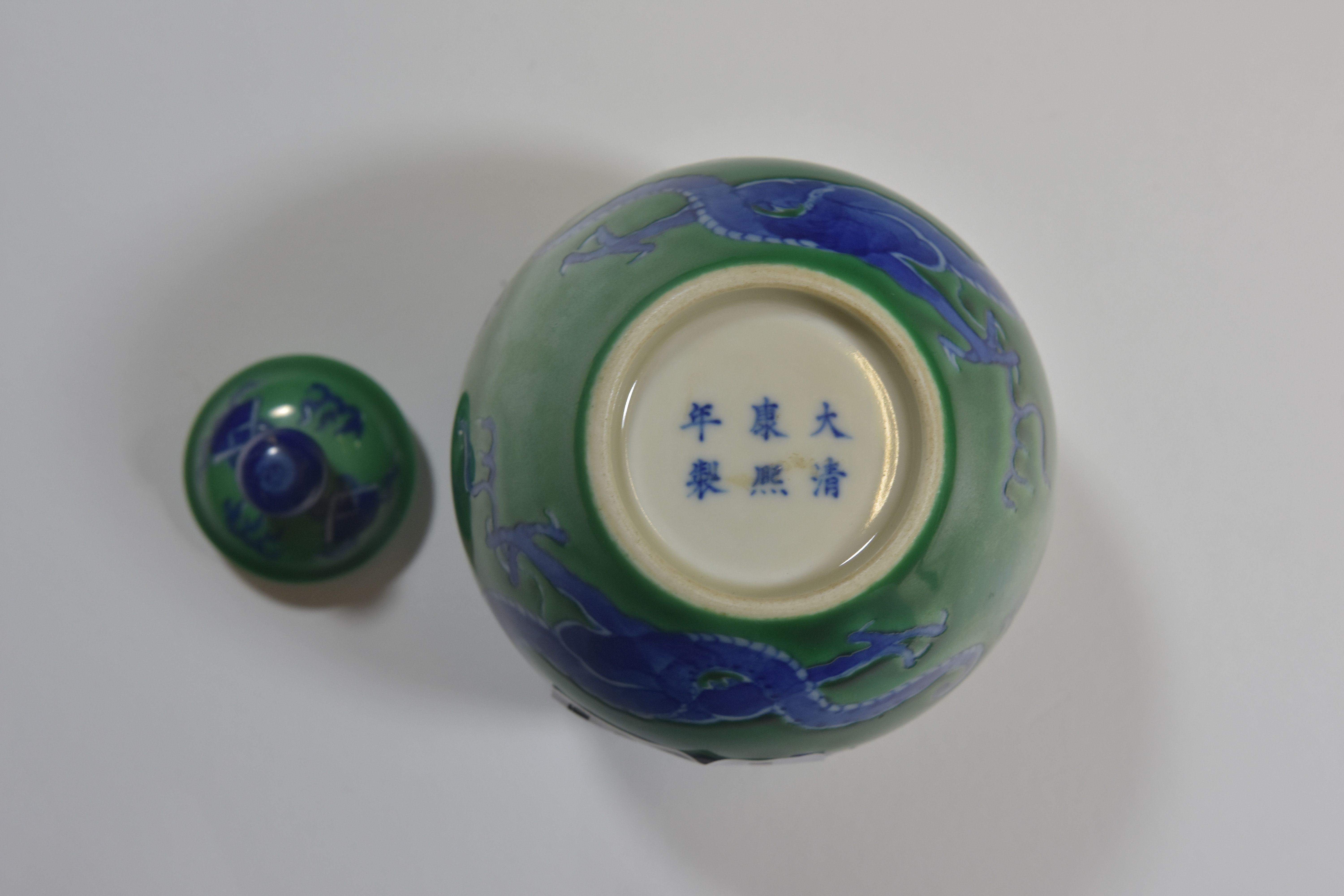 Lot 30 - A 19th century green glazed jar and cover with dragon Kangxi six character mark 15cm清朝時期 綠地藍龍小罐""