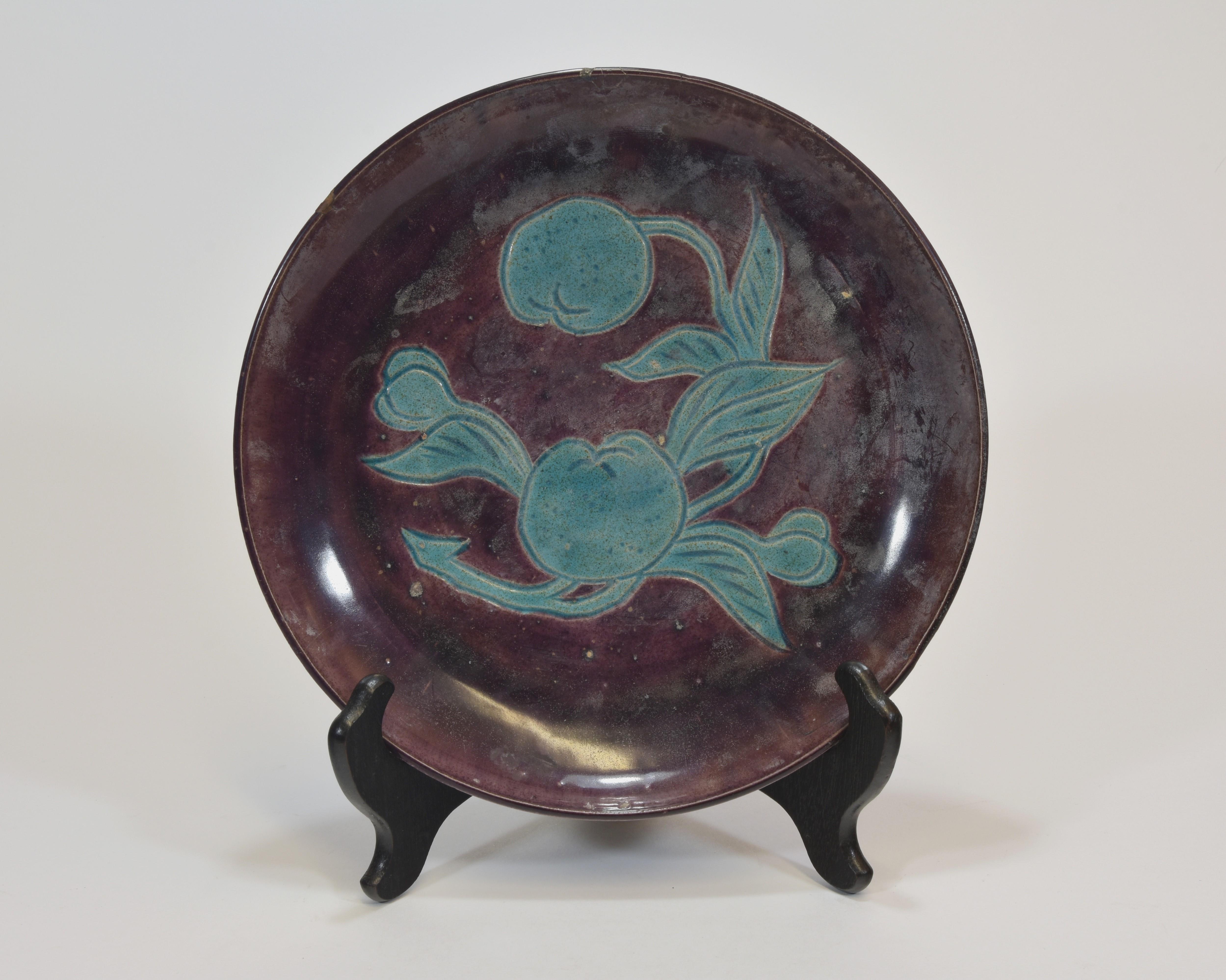 Lot 19 - An aubergine glazed dish with two peaches Kangxi period 25cm diameter清 康熙時期 茄子釉碟