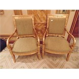 A pair of Empire style giltwood armchairs the back rest with panelled top rail decorated with