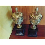 A pair of Italian Neoclassical gilt bronze urns cast in relief mounted on a black marble plinth