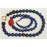 TWO SINGLE ROW LAPIS LAZULI BEAD NECKLACES, the first designed as a near uniform row of spherical