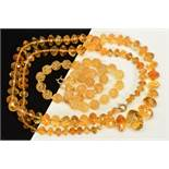 TWO CITRINE BEAD NECKLACES, the first designed as a uniform single row of carved spherical beads,