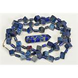 A LONG LAPIS LAZULI BEAD NECKLACE AND A LAPIS LAZULI PAPERWEIGHT, the necklace designed as cube