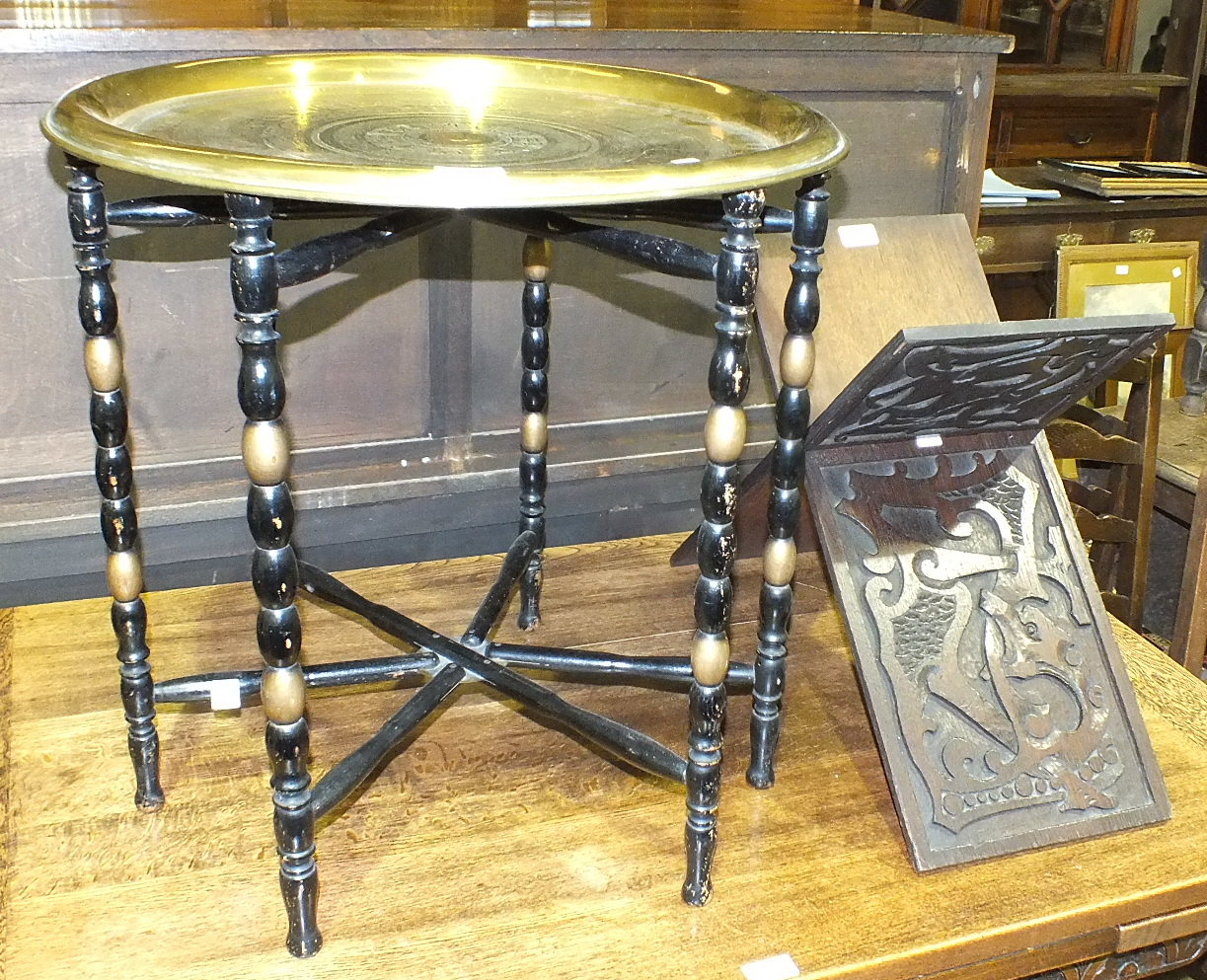 Lot 7 - A brass Benares tray on folding wooden stand and a carved wood folding Koran stand, (2).