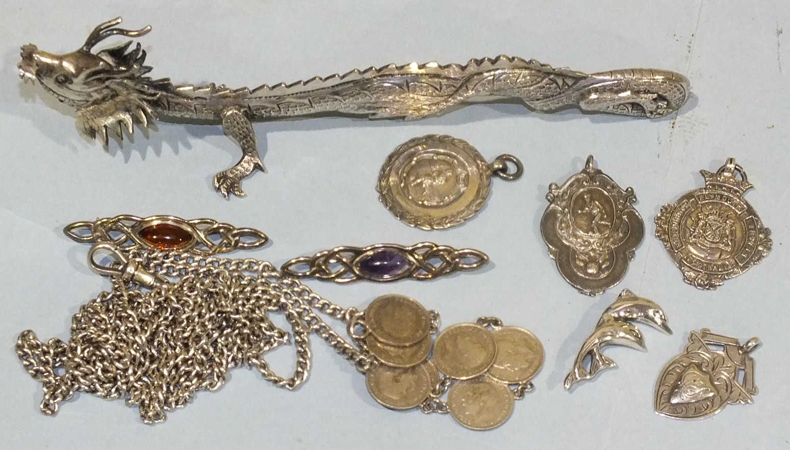 Lot 210 - A silver guard chain, various silver medallions, brooches and a Chinese white metal dragon, total