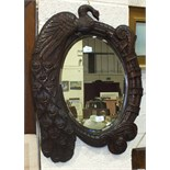 An oval bevelled mirror plate within a hardwood frame carved with a Peacock and engraved 'A Fair