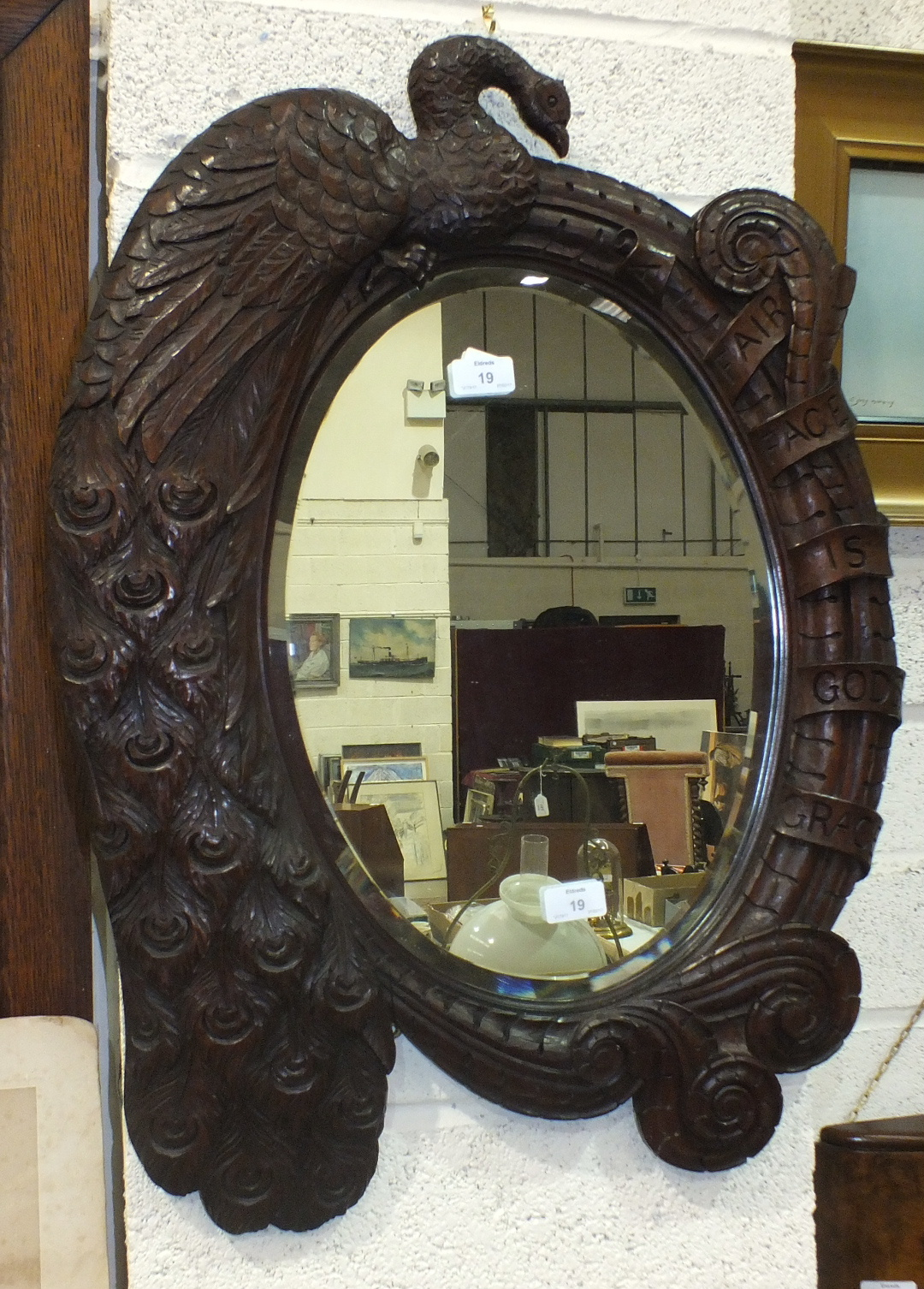 Lot 19 - An oval bevelled mirror plate within a hardwood frame carved with a Peacock and engraved 'A Fair