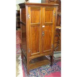 An early 20th century mahogany music cabinet, having a pair of panel doors enclosing ten shelves,