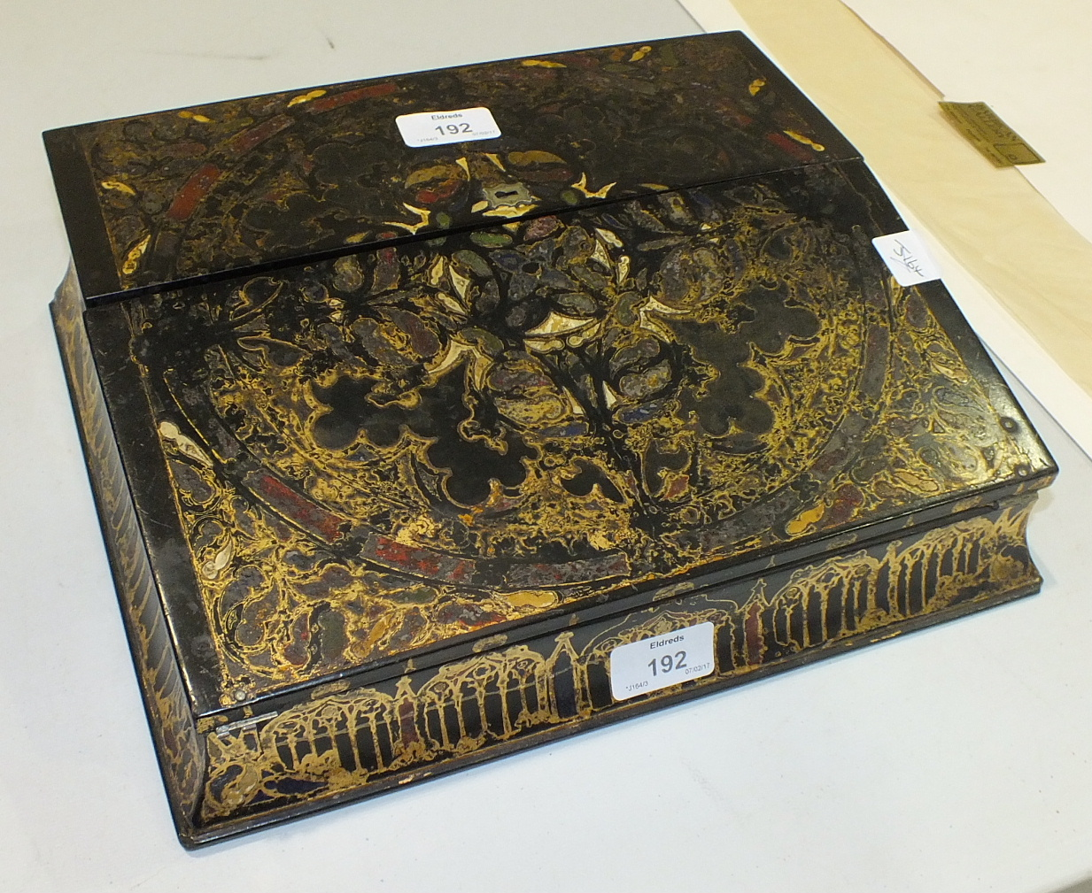 Lot 192 - An ebonised lacquered writing slope with hinged top revealing letter rack, inkstand and pen tray and