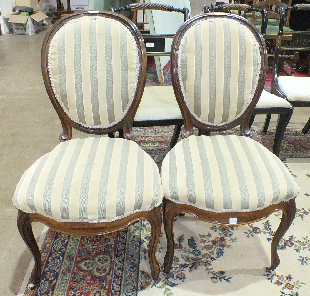 Lot 16 - A pair of Victorian rosewood salon dining chairs with upholstered seat and back, on cabriole front