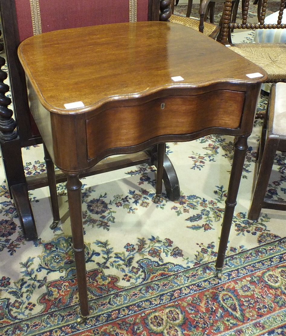 Lot 14 - A mahogany shaped side table fitted with a serpentine drawer, on turned legs with castors, 57cm