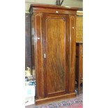 A late-19th/early-20th century mahogany wardrobe, the cornice above a single door, on plinth base,