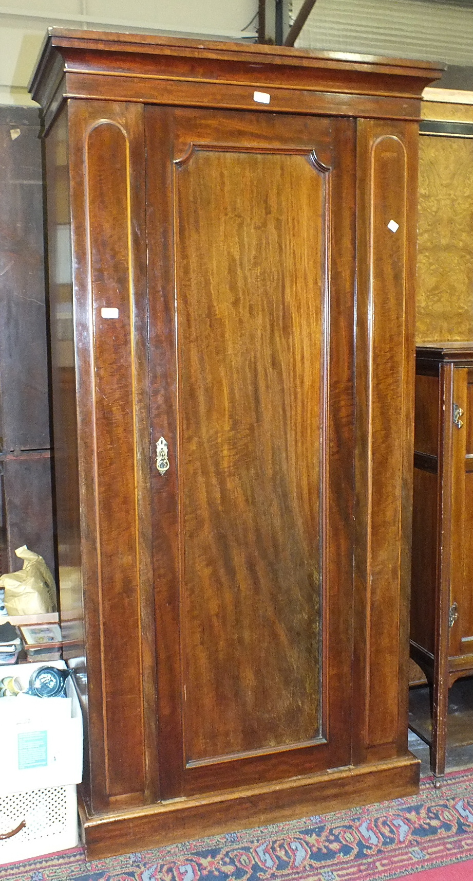 Lot 11 - A late-19th/early-20th century mahogany wardrobe, the cornice above a single door, on plinth base,