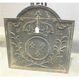 A reproduction cast iron fire back decorated with a crown above three fleur de lys within a circle