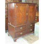 An early-19th century mahogany small linen press having a pair of panelled doors enclosing five