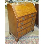 A reproduction walnut bureau, the fall front above two small and three long drawers, on bracket