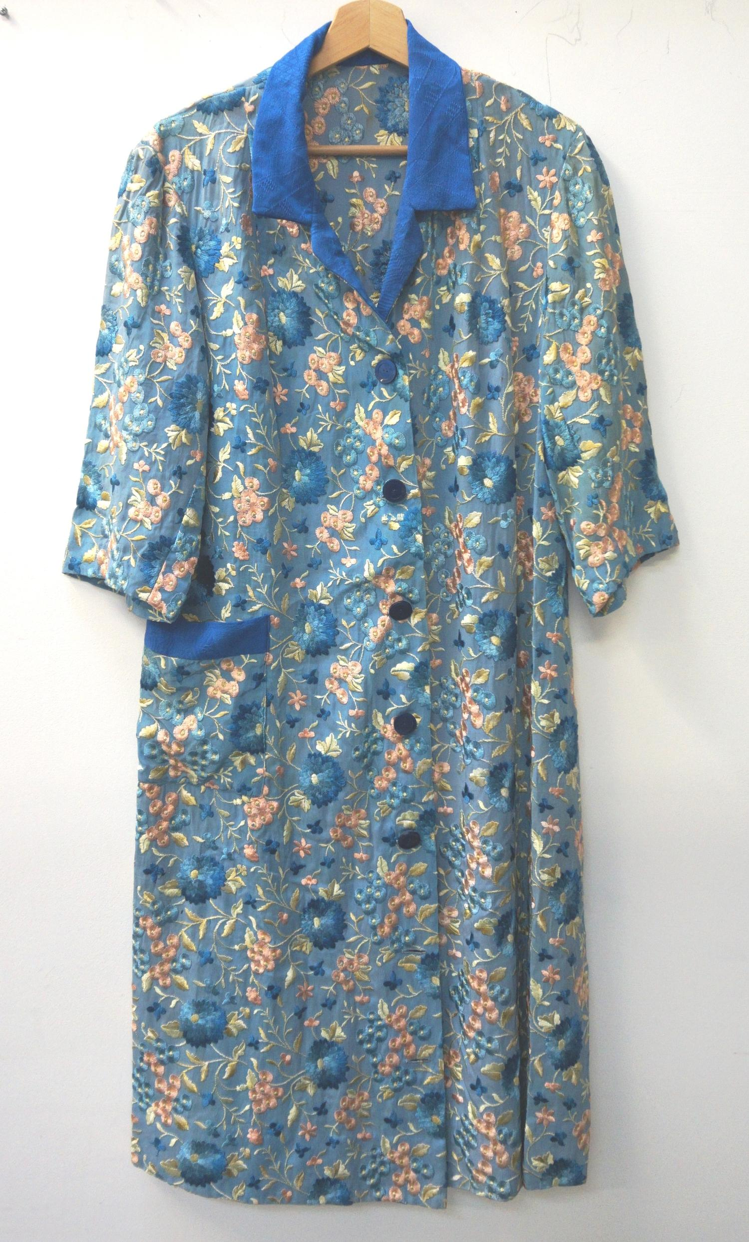 Lot 341 - CHINESE EMBROIDERED SILK AND COTTON LONG JACKET with a pale blue ground decorated with flowers and a