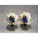 PAIR OF SAPPHIRE AND DIAMOND CLUSTER STUD EARRINGS the central oval cut sapphire on each in ten