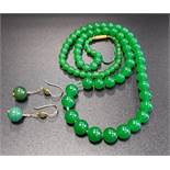 GRADUATED GREEN JADE BEAD NECKLACE 43.5cm long; together with a pair of nine carat gold mounted jade