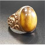 TIGER'S EYE DRESS RING the central oval cabochon tiger's eye flanked by relief scroll decorated