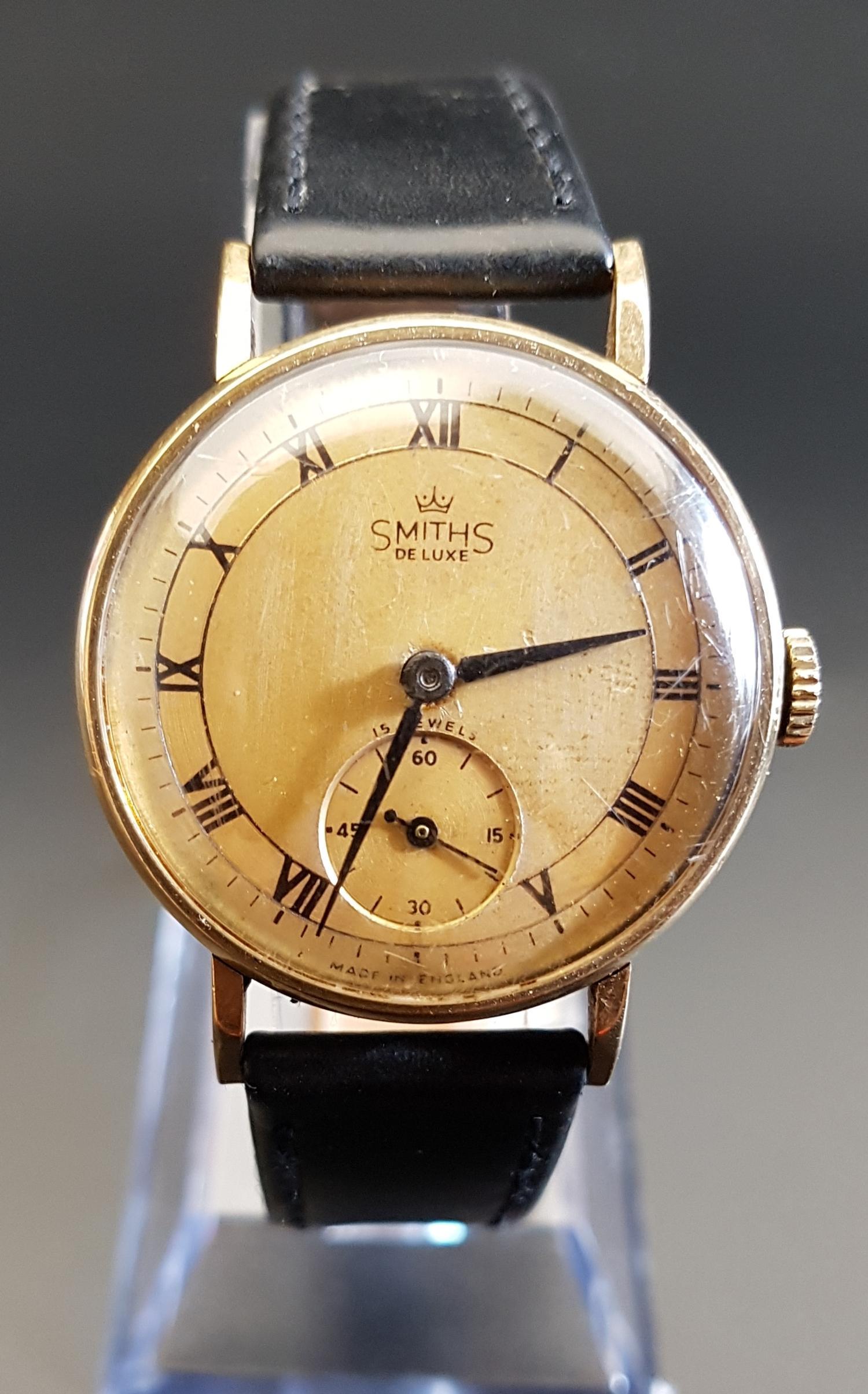 Lot 14 - GENTLEMAN'S NINE CARAT GOLD CASED SMITHS DE LUXE WRISTWATCH 1950s, the gilt dial with Roman numerals