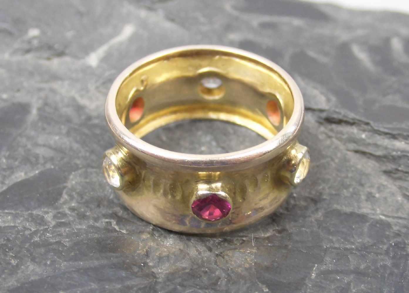 Lot 26 - RING, 333er Gelbgold (getestet, 5,8 g), breite Ringschiene besetzt mit Rubinen und weißen Safiren.