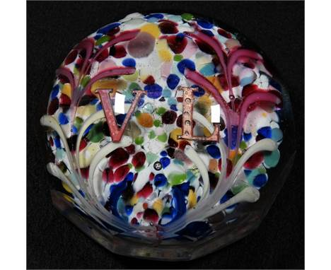 A late Victorian glass paperweight, the domed top enclosing a colourful Nailsea pad, centred by the initials V L and flanked