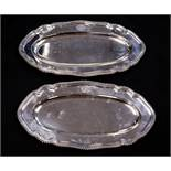 A pair of George V silver platters, elongated oval form, ogee gadrooned borders, with coat of arms,