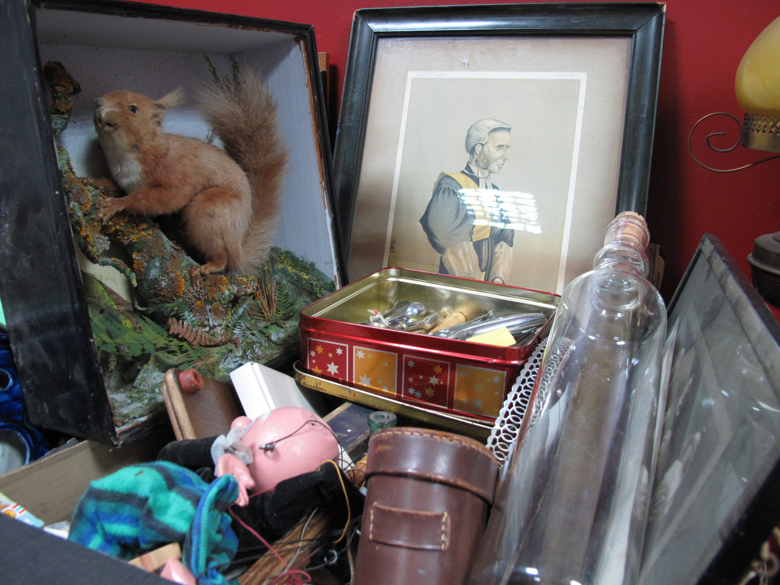 Lot 1002 - A Taxidermy Squirrel, glass rolling pin, garden syringe, quiz print, Pelham puppet, tie press,