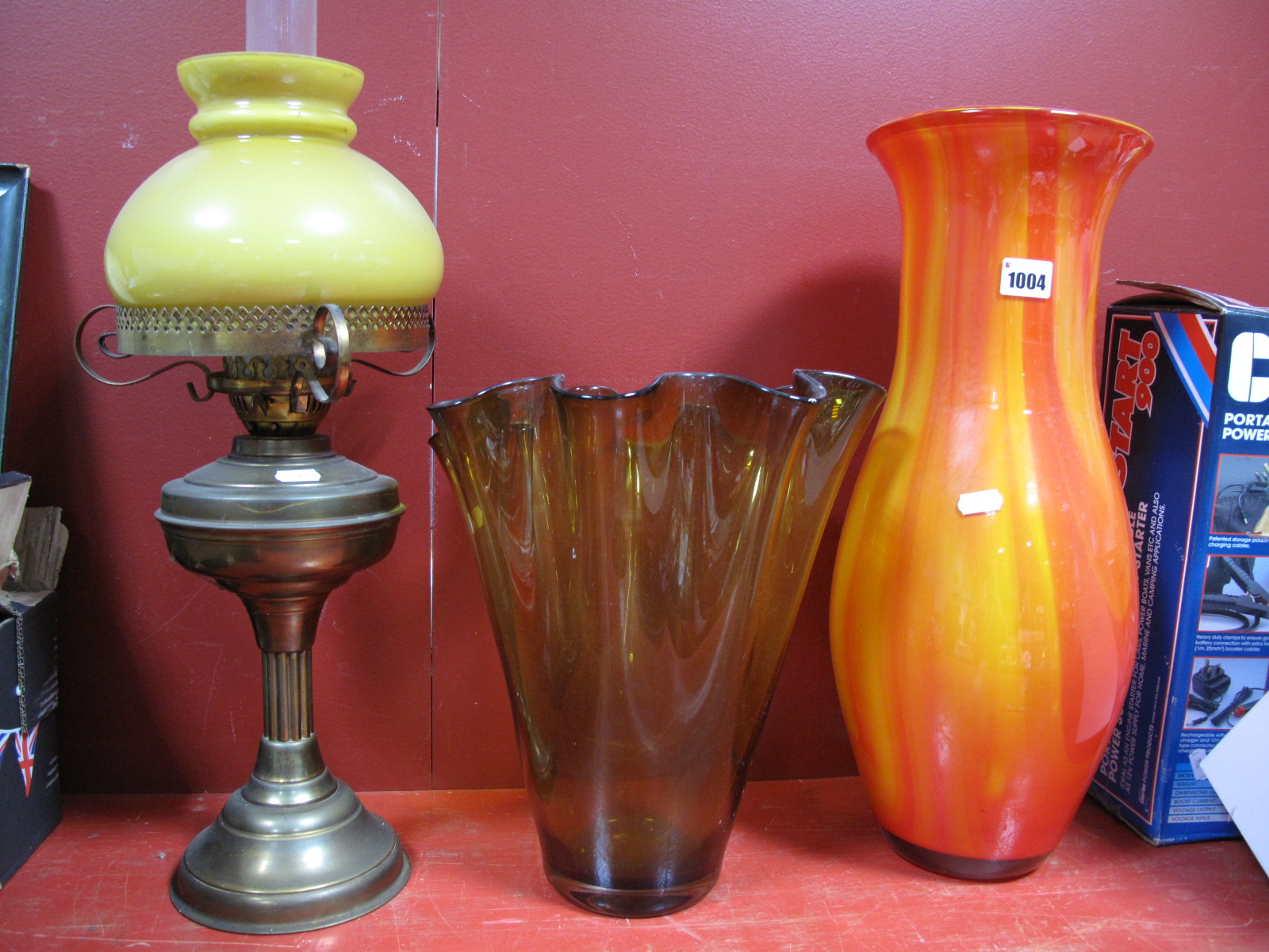 Lot 1004 - An Oil Lamp, red and amber streaked glass vase, yellow glass vase with wavy rim, 32cm high. (3)