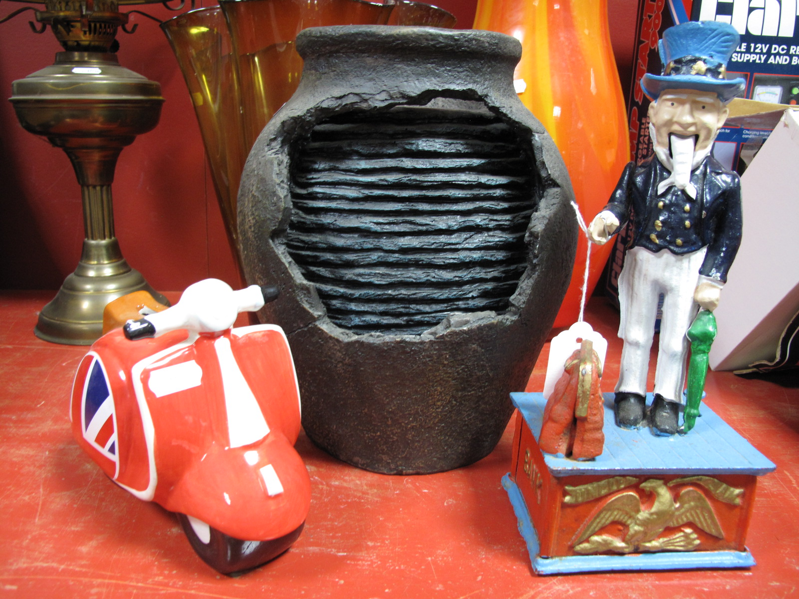 Lot 1006 - A Reproduction American 'Uncle Sam' Cast Iron Money Bank, a pottery scooter money bank and a vase