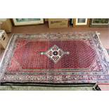 A Persian red ground floral rug,