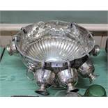 A silver plated punch set with lion ring handles and embossed floral decoration by Pinder Bros