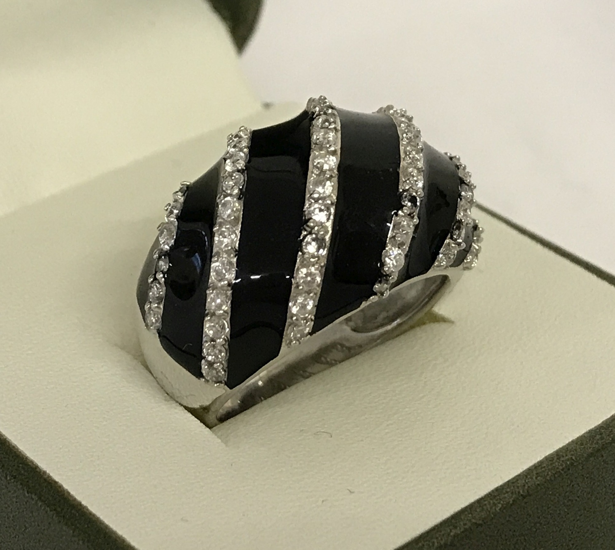 A ladies black enamel and clear stone set dome style dress ring.