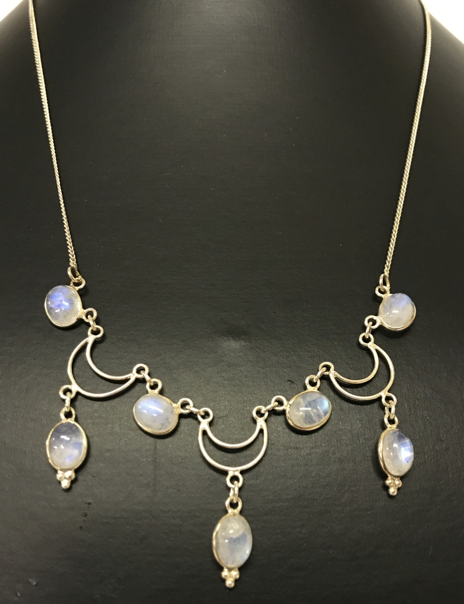 A decorative silver and moonstone necklace.