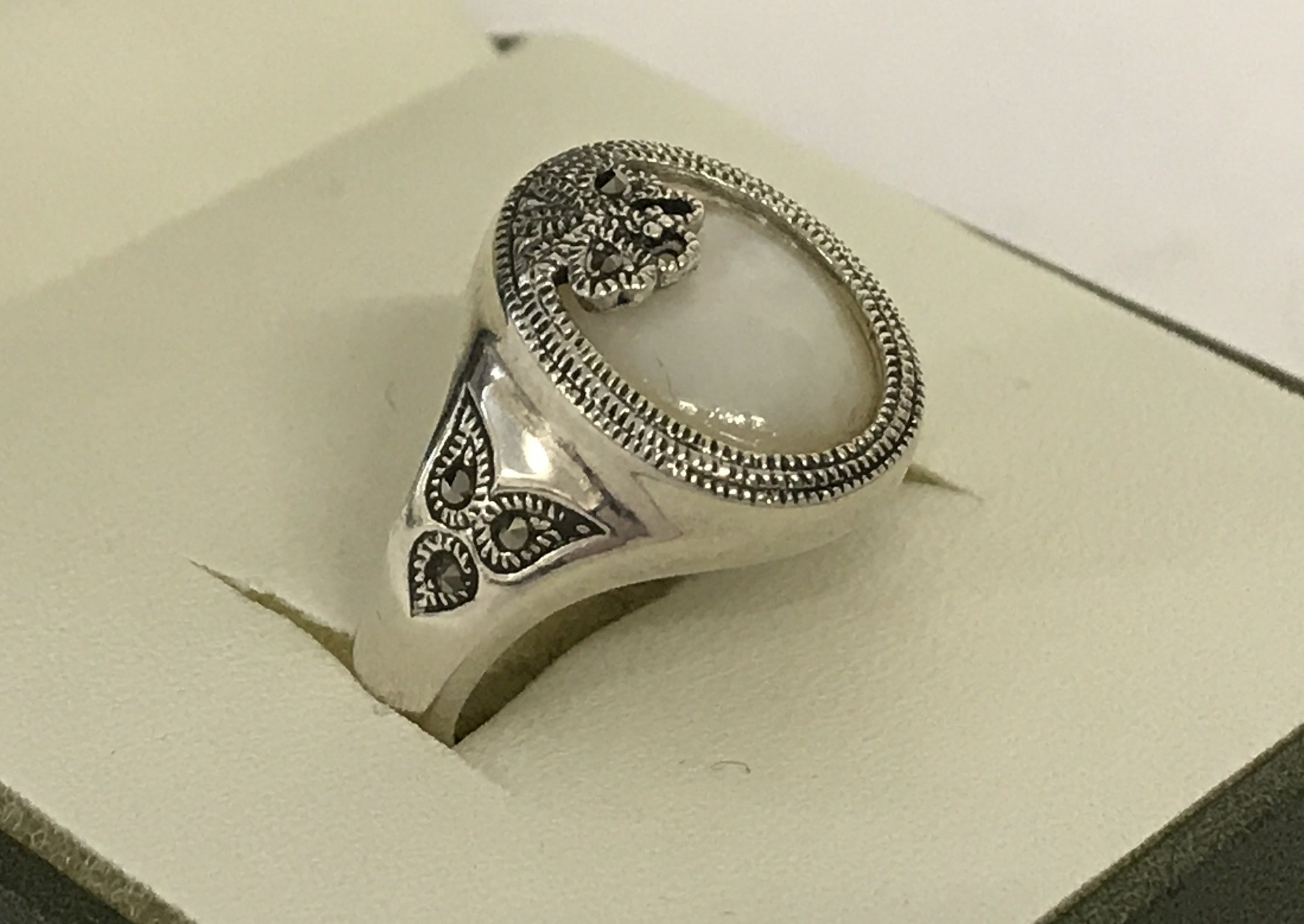 Lot 35 - A silver butterfly detail dress ring set with pearlised shell and marcasite's.