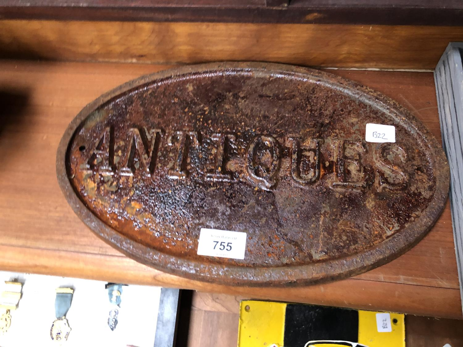 Lot 755 - A CAST IRON 'ANTIQUES' OVAL SIGN