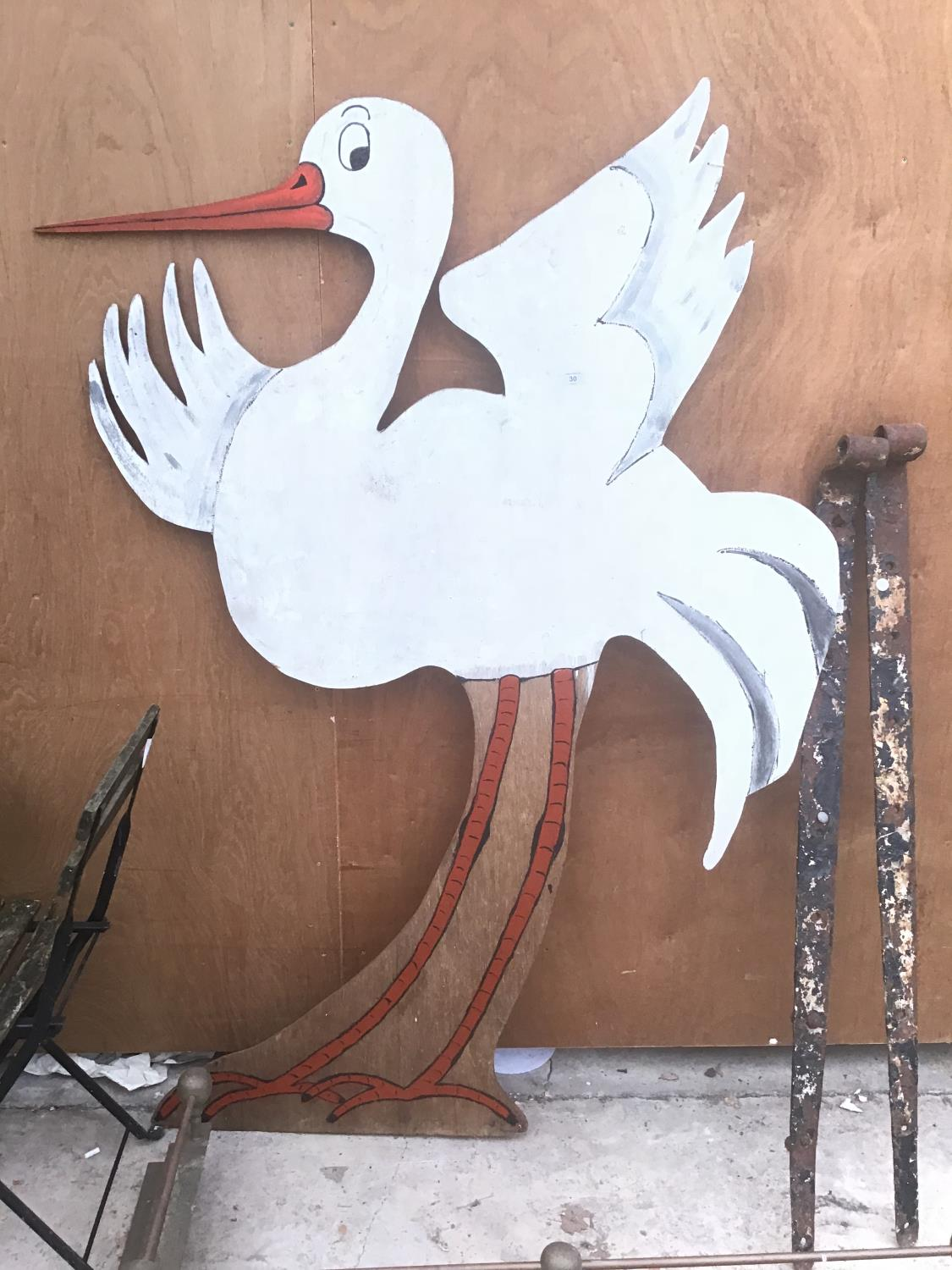 A LARGE WOODEN PAINTED CUT OUT OF A STORK