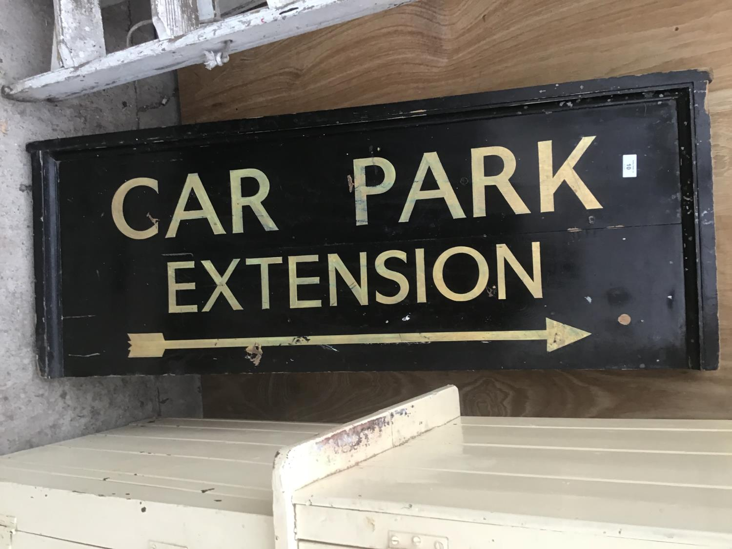 A WOODEN PAINTED 'CAR PARK EXTENSION' SIGN