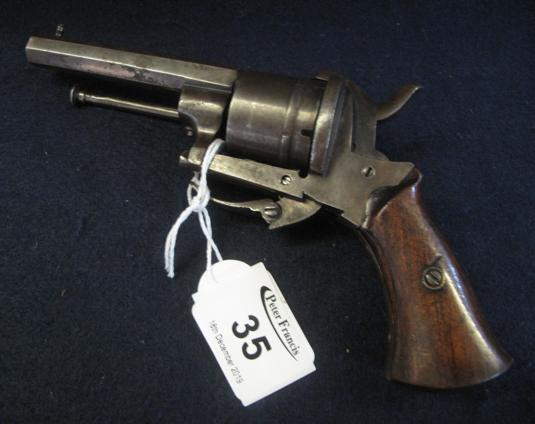 Late 19th Century pin fire revolver having wooden grips and integral ramrod.